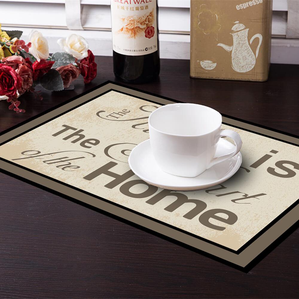 """פלייסמנט מעוצב בצבעים חומים עם משפט """"המטבח הוא לב הבית"""" מעליו כוס קפה על שולחן פורמייקה"""