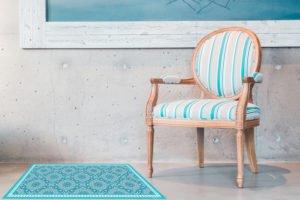 שטיח פי ויסי בגוונים טורקיזים עזים בסגנון טורקי על רצפת בטון עם קיר בטון ולידו כסא ענתיקה מרופד בטורקיז ואפור