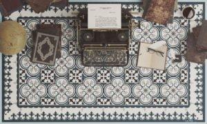 שטיח פי ויסי בגוונים כחולים וחומים מונח כמה מתחת למכונת כתיבה ספרים עתיקים יומן עם עט נוצה משקפיים וגלובוס
