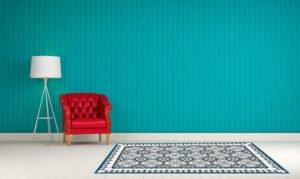 עיצוב גרפי של שטיח פי וי סי בגוונים כחולים מונח על פרקט לבן קיר טורקיז חזק כורסה לכה אדומה ומנורה לבנה