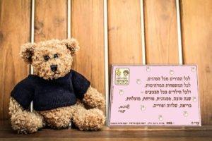 ברכת שנה טובה מותאמת לעסק של טיפטיפה על רקע עץ חום עם דובי ליד
