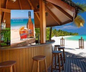 קאפה לשפריצוזו מונחת על בר בקריביים עם ים ברקע וכסאות גבוהים