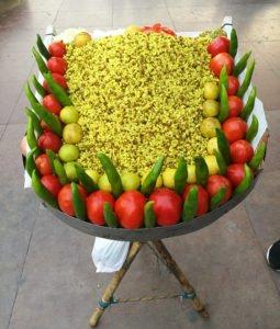 תמונה של אוכל רחוב הודי מעוצב יפה אוכל צהוב עם עגבניות ופלפלים מסביב
