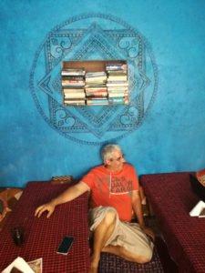 איש יושב בבית קפה הודי עם איור מנדלה גדול סביב מדף ספרים על רקע קיר כחול