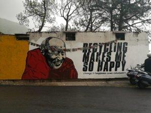 גרפיטי עם תמונה של הדלאי לאמה ומשפט מיחזור עושה אותי כל כך מאושר עיצוב גרפי ברחוב
