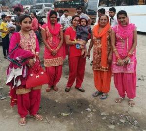 חבורה מקסימה של נשים הודיות לבושות באותם הגוונים מסביבם הודים ואוטובוסים