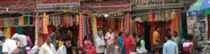 תמונת שוק בהודו עם כמות סארי ענקית במגוון צבעים ברקע והמון אנשים לבושים צבעוניים לפניהם