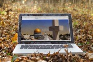 צילום מסך של ישראלנדו - דף הבית. תמונה של מסגד אל אקצה מרחוק ומקרוב יש צלב מטושטש על שליש מסך