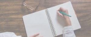 רקע לפולד של אישה שכותבת במחברת שמונחת על שולחן עץ עם משקפיים ועיפרון טורקיז