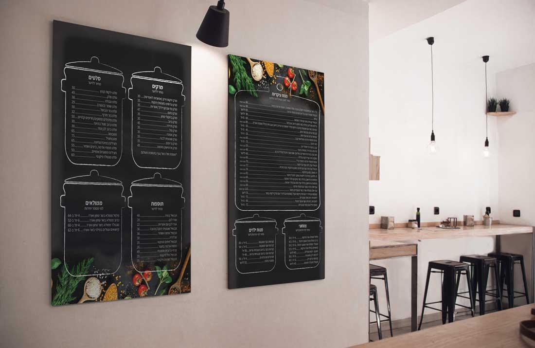 תפריט שחור עם ירקות מסבחיב כתוב בגיר על נייר דמוי לוח תלוי על קיר במסעדה